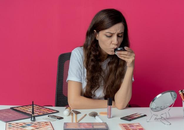 Onaangenaam jong mooi meisje zittend aan make-up tafel met make-up tools houden en kijken naar poeder geïsoleerd op karmozijnrode achtergrond