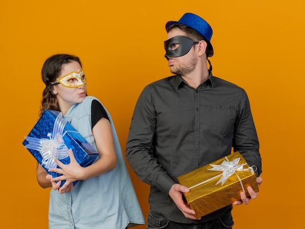 Onaangenaam jong partijpaar bekijkt elkaar die giftdozen houden die maskeradeoogmasker dragen dat op oranje wordt geïsoleerd