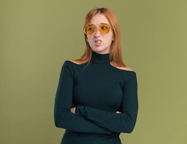 Onaangenaam jong roodharig gembermeisje met sproeten in zonnebril die zich met gekruiste wapens bevinden die kant op olijfgroen bekijken