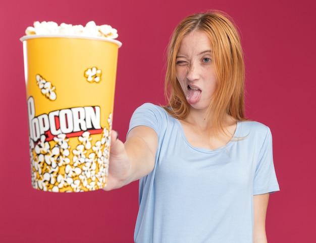 Onaangenaam jong roodharige gembermeisje met sproeten steekt tong uit terwijl ze popcornemmer vasthoudt en kijkt geïsoleerd op roze muur met kopieerruimte