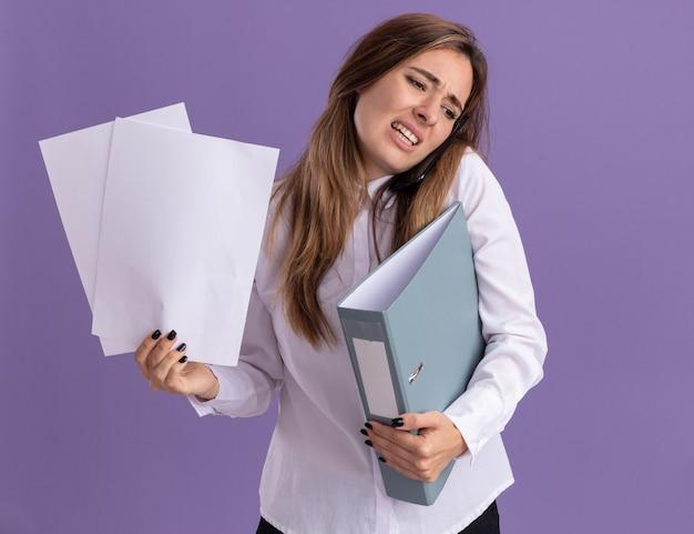 Onaangenaam jong, vrij blank meisje houdt vellen papier en een bestandsmap die aan de telefoon praat, geïsoleerd op een paarse muur met kopieerruimte