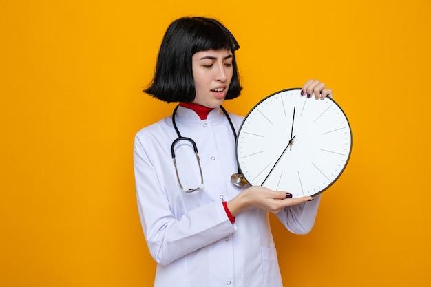 Onaangenaam jong, vrij kaukasisch meisje in doktersuniform met een stethoscoop die de klok vasthoudt en bekijkt