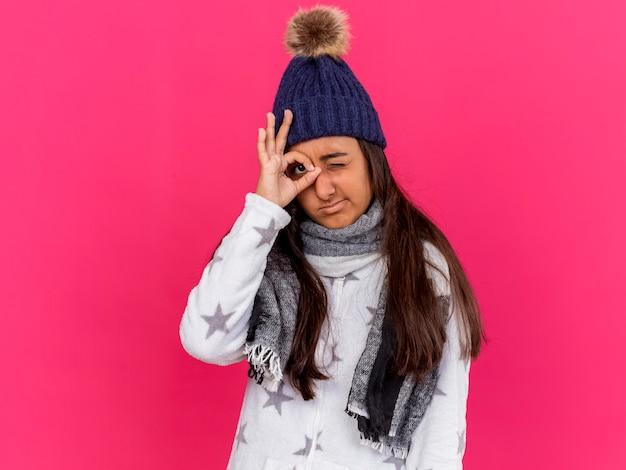 Onaangenaam jong ziek meisje dat de winterhoed met sjaal draagt die blikgebaar toont dat op roze wordt geïsoleerd