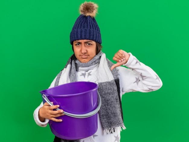 Onaangenaam jong ziek meisje dat de winterhoed met sjaal draagt die plastic emmer houdt die duim toont die neer op groen wordt geïsoleerd