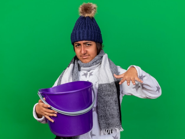 Onaangenaam jong ziek meisje dat de winterhoed met sjaal draagt die plastic emmer houdt die op groen wordt geïsoleerd