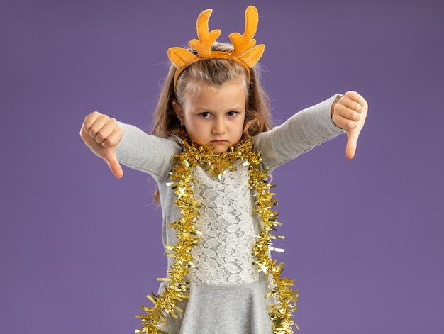 Onaangenaam meisje dat de hoepel van het kerstmishaar met slinger op hals draagt die duimen toont die neer op blauwe achtergrond wordt geïsoleerd