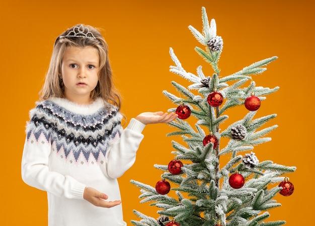 Onaangenaam meisje dat zich dichtbij kerstboom bevindt die tiara met slinger op halspunten aan kant draagt die op oranje achtergrond wordt geïsoleerd