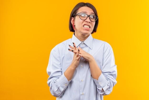 Onaangenaam uitziende jonge, mooie meid met een bril die handen bij elkaar houdt, geïsoleerd op een oranje muur