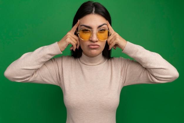 Onaangenaam vrij donkerbruin kaukasisch meisje in zonnebril legt vingers op tempels op groen