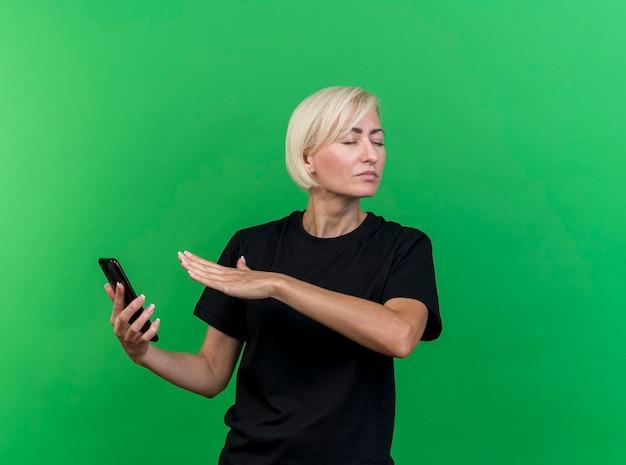 Onaangename blonde slavische vrouw van middelbare leeftijd die mobiele telefoon houdt die hand in lucht houdt die geen gebaar met gesloten ogen doet geïsoleerd op groene muur met exemplaarruimte