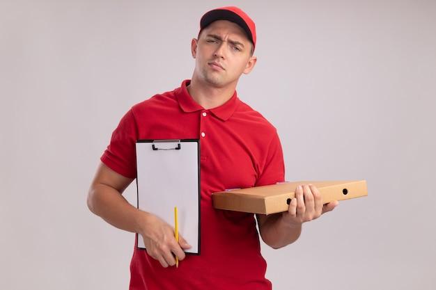 Onaangename jonge bezorger die eenvormig met glb draagt die klembord met pizzadoos houdt die op witte muur wordt geïsoleerd