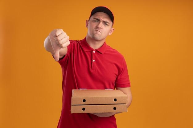 Onaangename jonge bezorger die uniform met pet draagt die pizzadozen houdt die duim omlaag tonen geïsoleerd op oranje muur