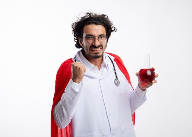 Onaangename jonge blanke man in optische bril dragen arts uniform met rode mantel en met een stethoscoop om de nek houdt vuist en houdt rode chemische vloeistof in glazen kolf op witte muur