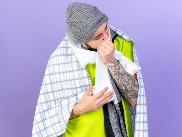 Onaangename jonge blanke zieke man gewikkeld in plaid met muts en sjaal houdt en veegt neus met wc-papier geïsoleerd op paarse muur met kopie ruimte