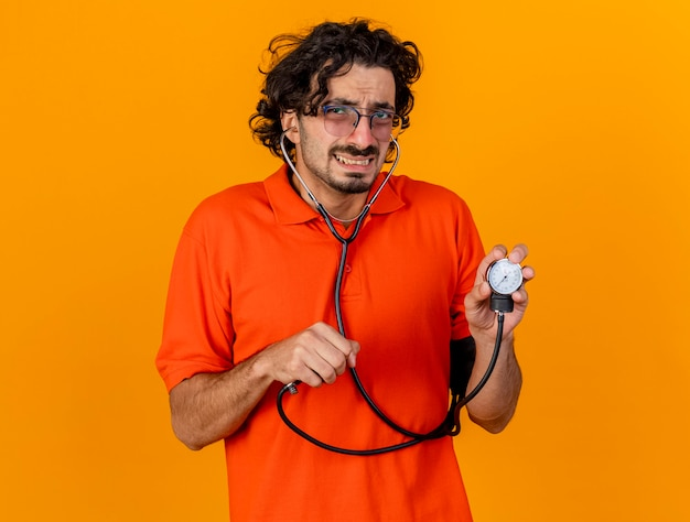 Onaangename jonge blanke zieke man met bril en stethoscoop met bloeddrukmeter geïsoleerd op oranje muur met kopie ruimte