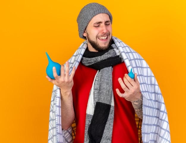 Onaangename jonge blanke zieke man met muts en sjaal gewikkeld in plaid houdt klysma
