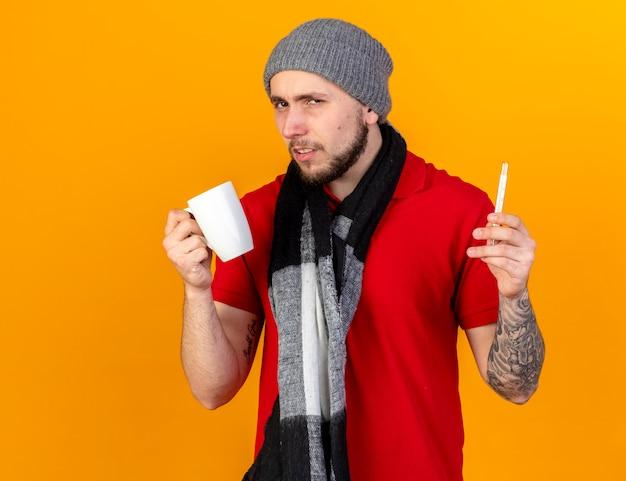Onaangename jonge blanke zieke man met winter hoed en sjaal houdt beker en thermometer op oranje