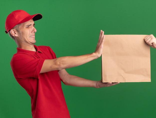 Onaangename jonge blonde bezorger geeft papieren pakket aan iemand op groen