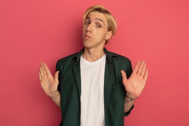 Onaangename jonge blonde kerel die groen t-shirt draagt dat stopgebaar toont