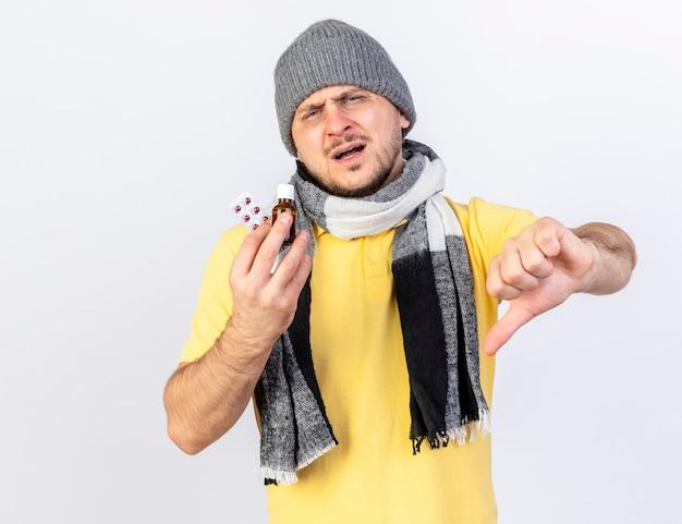 Onaangename jonge blonde zieke man met winter muts en sjaal duimen naar beneden en houdt geneeskunde in glazen fles en pakje medische pillen geïsoleerd op witte muur