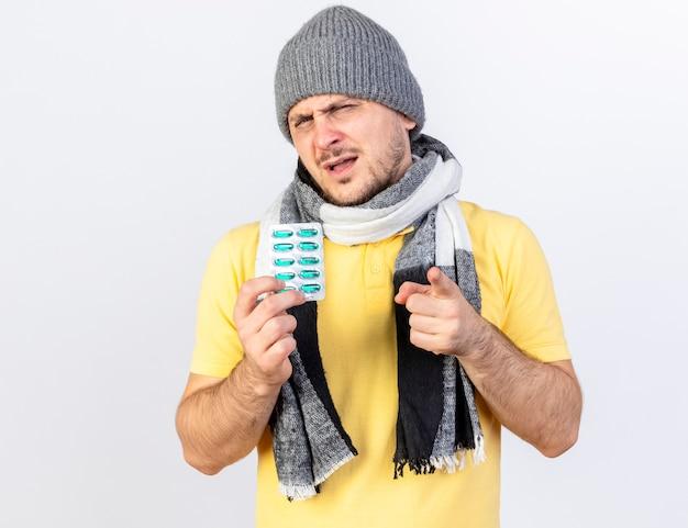 Onaangename jonge blonde zieke man met winter muts en sjaal houdt pakje medische pillen en punten aan de voorkant geïsoleerd op een witte muur