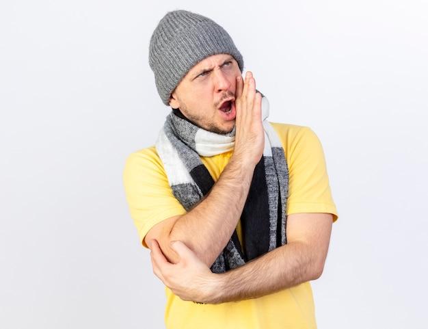 Onaangename jonge blonde zieke slavische man met muts en sjaal houdt handen dicht bij de mond kijken kant iemand bellen geïsoleerd op een witte muur met kopie ruimte