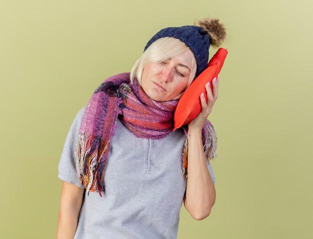 Onaangename jonge blonde zieke slavische vrouw die de winterhoed draagt
