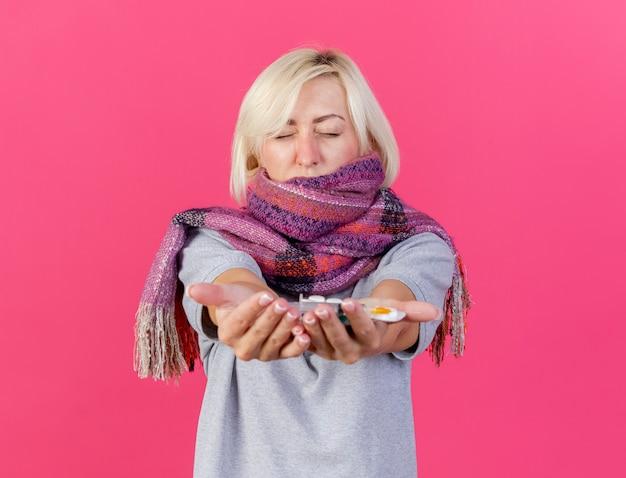 Onaangename jonge blonde zieke slavische vrouw die sjaal draagt houdt verpakkingen van medische pillen