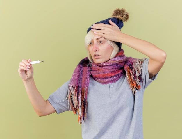 Onaangename jonge blonde zieke slavische vrouw met winter muts en sjaal legt hand op hoofd kijken naar thermometer geïsoleerd op olijfgroene muur met kopie ruimte