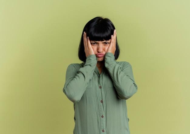 Onaangename jonge brunette blanke vrouw legt handen op gezicht geïsoleerd op olijfgroene achtergrond met kopie ruimte