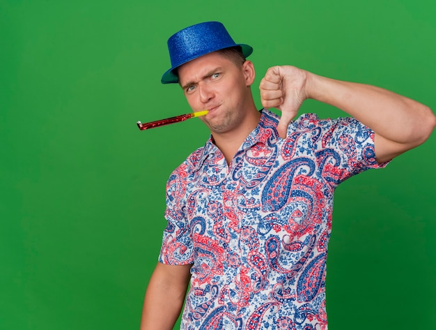 Onaangename jonge feestman die blauwe hoed draagt ?? blazende partijventilator die duim toont die neer op groen wordt geïsoleerd
