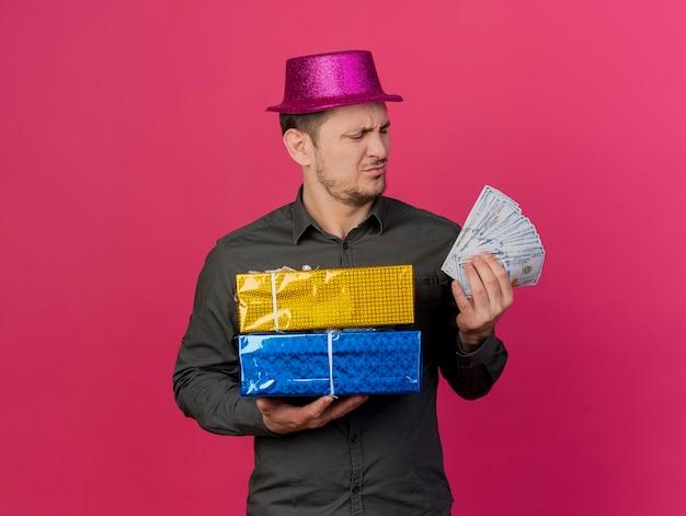 Onaangename jonge feestmens die een roze hoed draagt die geschenkdozen houdt en naar contant geld in zijn hand kijkt dat op roze wordt geïsoleerd