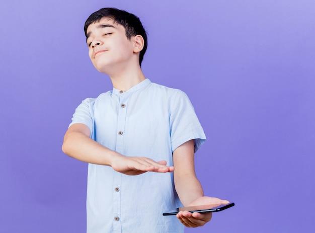 Onaangename jonge jongen die mobiele telefoon houdt die geen gebaar met hand met gesloten ogen doet die op purpere muur wordt geïsoleerd