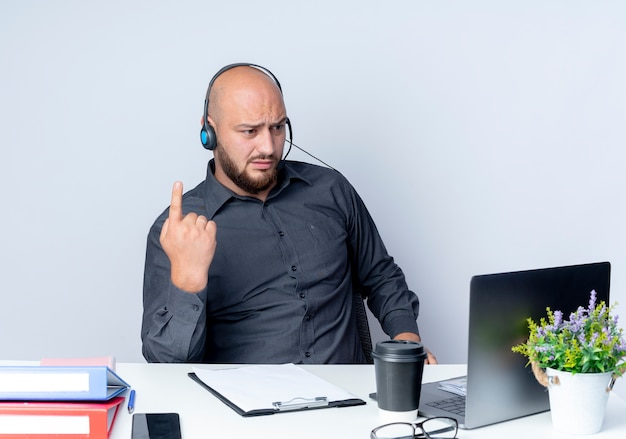 Onaangename jonge kale callcentermens die hoofdtelefoon draagt die aan bureau met werkhulpmiddelen zit die vinger opheft en laptop bekijkt die op witte achtergrond wordt geïsoleerd