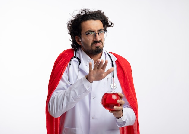 Onaangename jonge kaukasische superheld man in optische bril dragen uniform van de arts met rode mantel en met een stethoscoop om de nek houdt hand over rode chemische vloeistof in glazen kolf