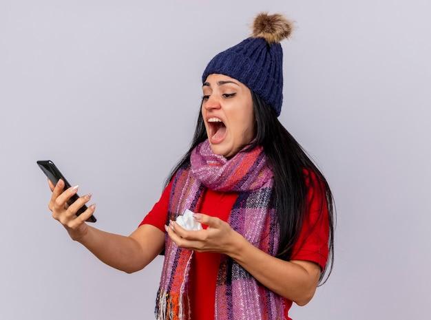 Onaangename jonge kaukasische ziek meisje dragen winter hoed en sjaal houden en kijken naar mobiele telefoon met servet in de hand geïsoleerd op een witte achtergrond met kopie ruimte