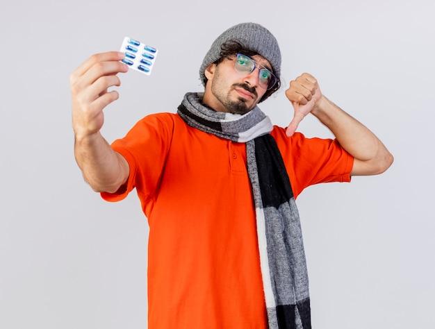 Onaangename jonge kaukasische zieke man met bril, muts en sjaal weergegeven: pack van medische capsules en duim omlaag kijken naar camera geïsoleerd op witte achtergrond