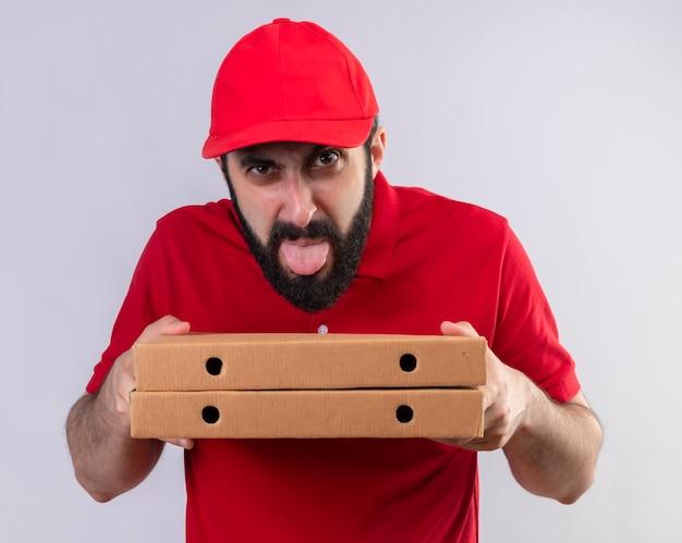 Onaangename jonge knappe blanke bezorger die rode uniform en pet draagt die pizzadozen houdt en tong toont die op witte achtergrond wordt geïsoleerd