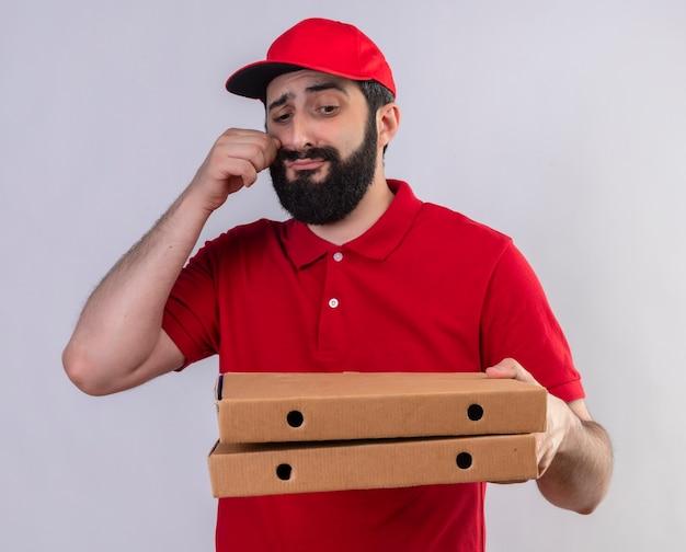 Onaangename jonge knappe blanke bezorger met rode uniform en pet houden en kijken naar pizzadozen met hand in de buurt van gezicht geïsoleerd op een witte achtergrond