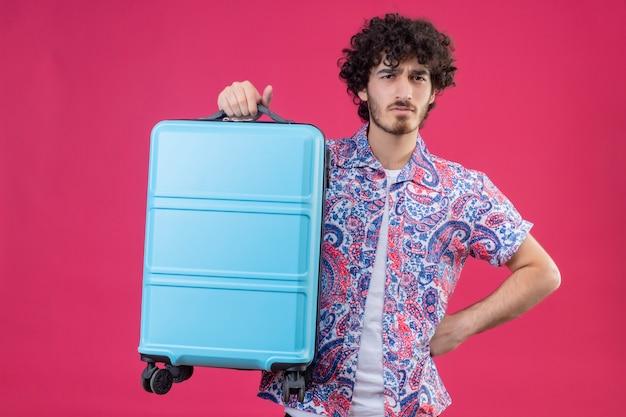 Onaangename jonge knappe gekrulde reizigersmens die koffer met hand op taille op geïsoleerde roze muur opheft