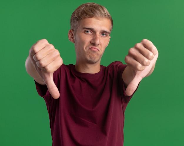 Onaangename jonge knappe kerel die rood overhemd draagt dat duimen toont die neer op groene muur wordt geïsoleerd