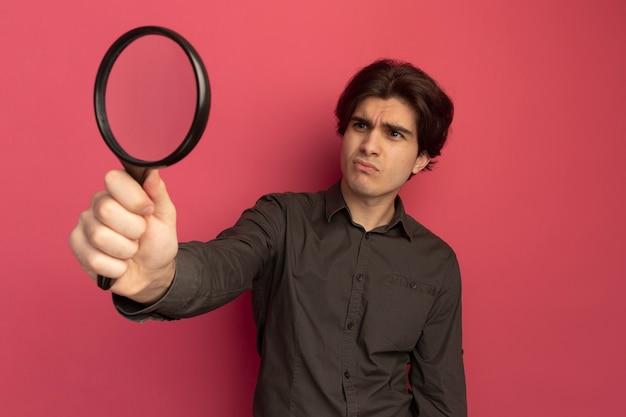 Onaangename jonge knappe kerel die zwart t-shirt draagt ?? en vergrootglas bekijkt dat op roze muur wordt geïsoleerd