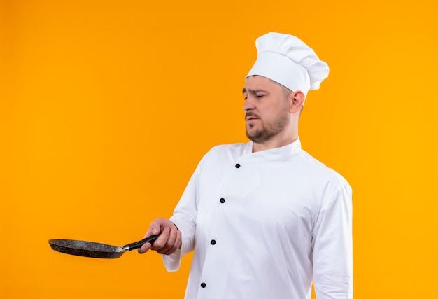 Onaangename jonge knappe kok in chef-kok uniform houden en kijken naar koekenpan geïsoleerd op oranje ruimte