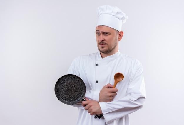 Onaangename jonge knappe kok in de koekenpan en de lepel van de chef-kok de eenvormige holding die kant bekijken die op witte ruimte wordt geïsoleerd
