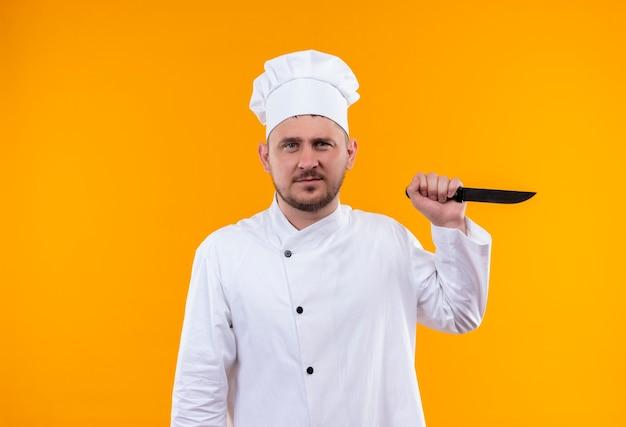 Onaangename jonge knappe kok in mes van de chef-kok het eenvormige bedrijf dat op oranje ruimte wordt geïsoleerd