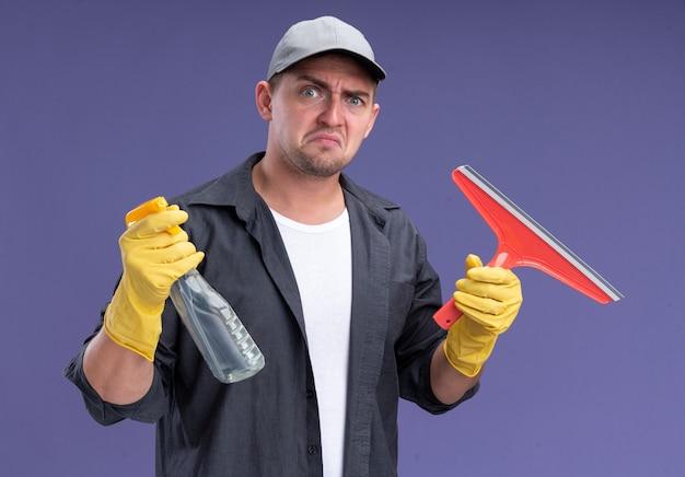 Onaangename jonge knappe schoonmaakster die t-shirt met pet en handschoenen draagt die zwabberhoofd en spuitfles houden die op purpere muur wordt geïsoleerd