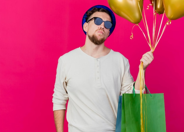 Onaangename jonge knappe slavische feestmens die feestmuts en zonnebril draagt ?? die ballonnen en papieren zakken houdt die naar voren kijken geïsoleerd op roze muur met kopie ruimte