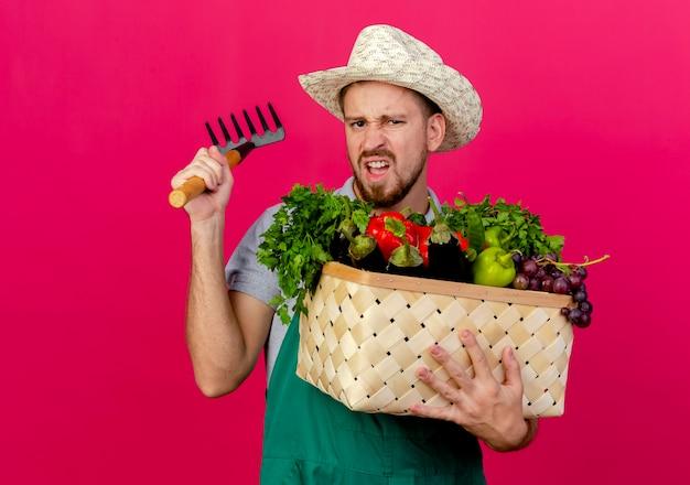 Onaangename jonge knappe slavische tuinman in uniform en hoed met mand met groenten en hark geïsoleerd op karmozijnrode muur