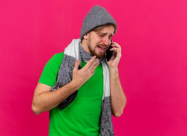 Onaangename jonge knappe slavische zieke man met winter muts en sjaal praten aan de telefoon hand in de lucht houden met gesloten ogen geïsoleerd op roze muur met kopie ruimte
