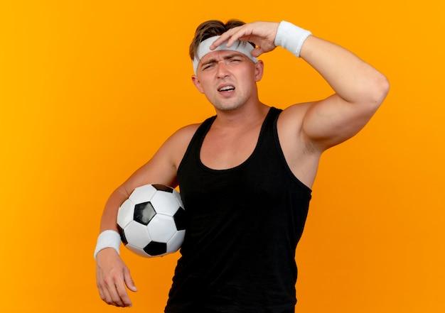 Onaangename jonge knappe sportieve man met hoofdband en polsbandjes houden van voetbal en zetten hand in de buurt van hoofd geïsoleerd op een oranje achtergrond